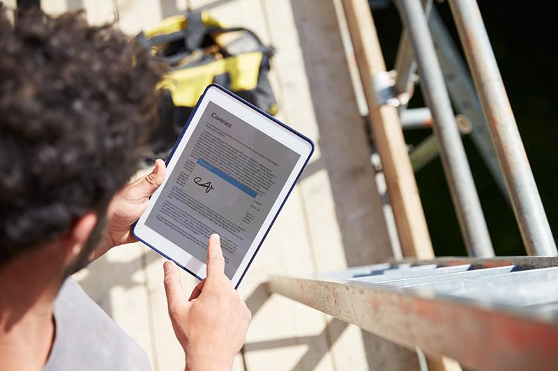 Homem assinando um contrato de locação digital em seu tablet.